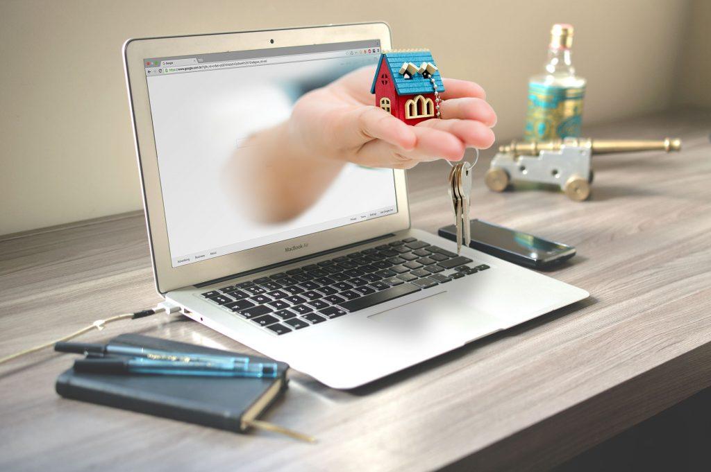 um notebook com uma mão saindo da tela segurando uma casa em miniatura