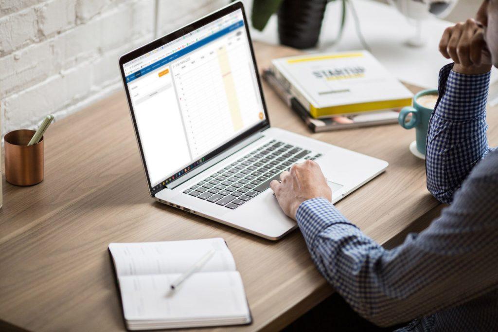 notebook sobre uma mesa e um homem digitando