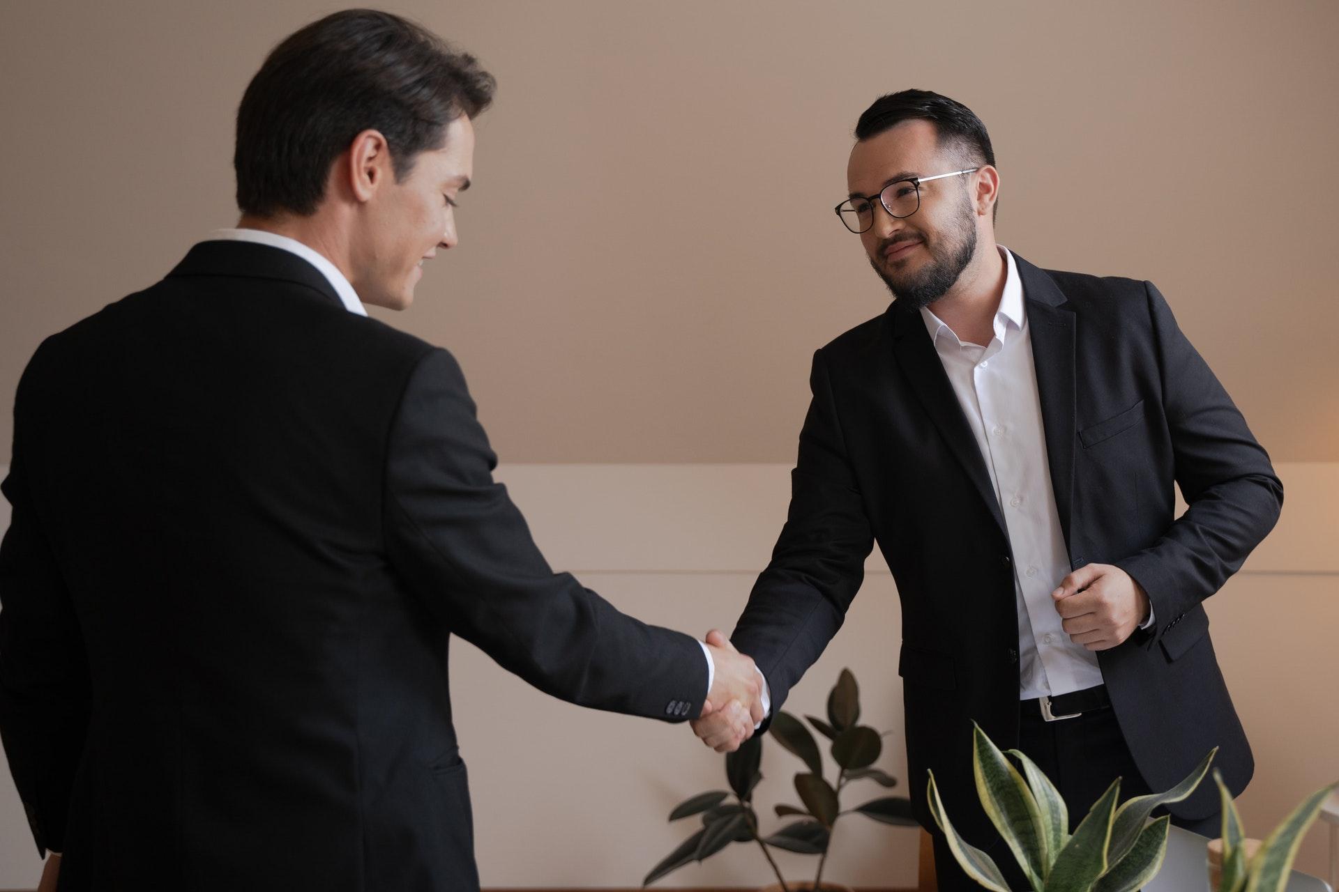 dois homens se cumprimentando com um aperto de mãos