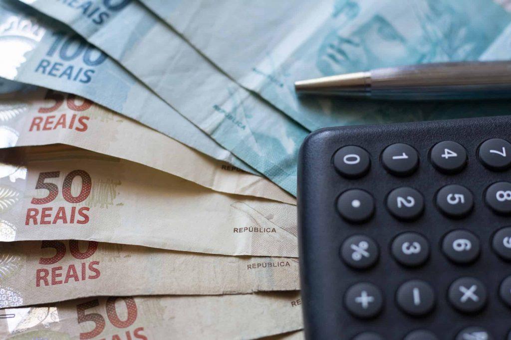 notas de dinheiro e calculadora mostram quanto ganha um corretor de imóveis