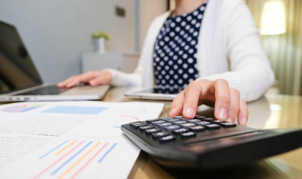 mulher calculando comissão do corretor na venda de imóveis